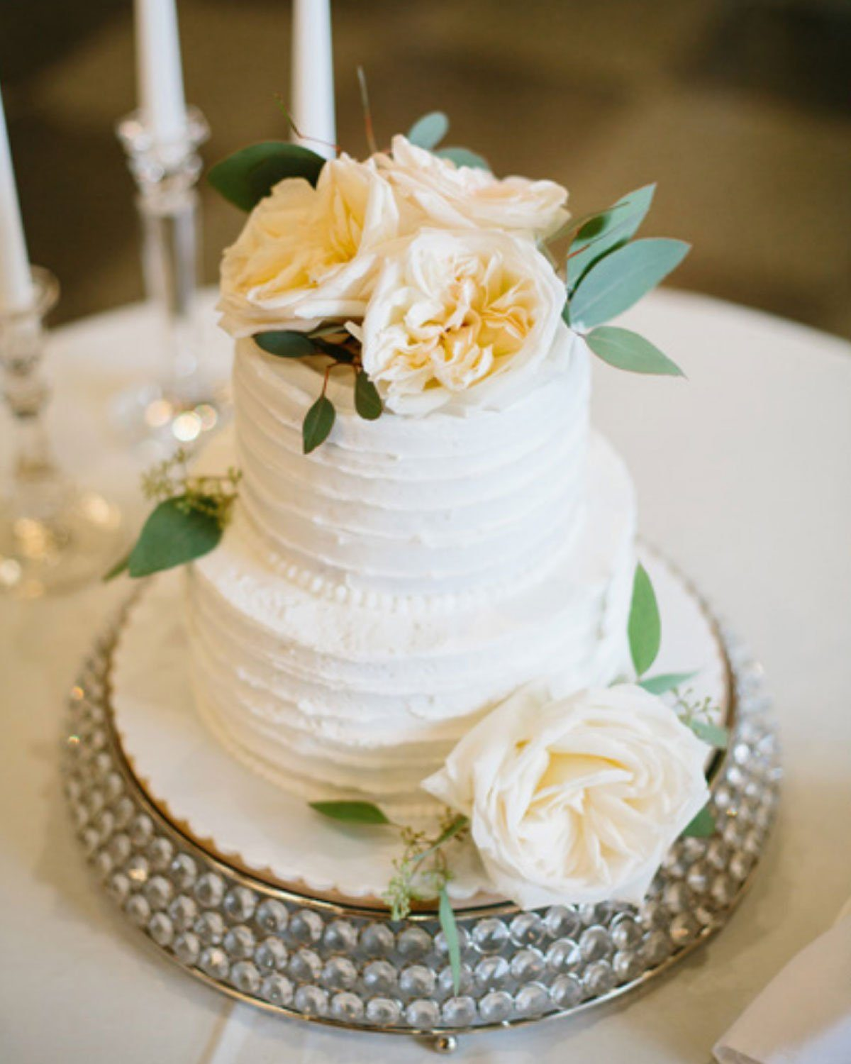 simple round white cake with white garden roses