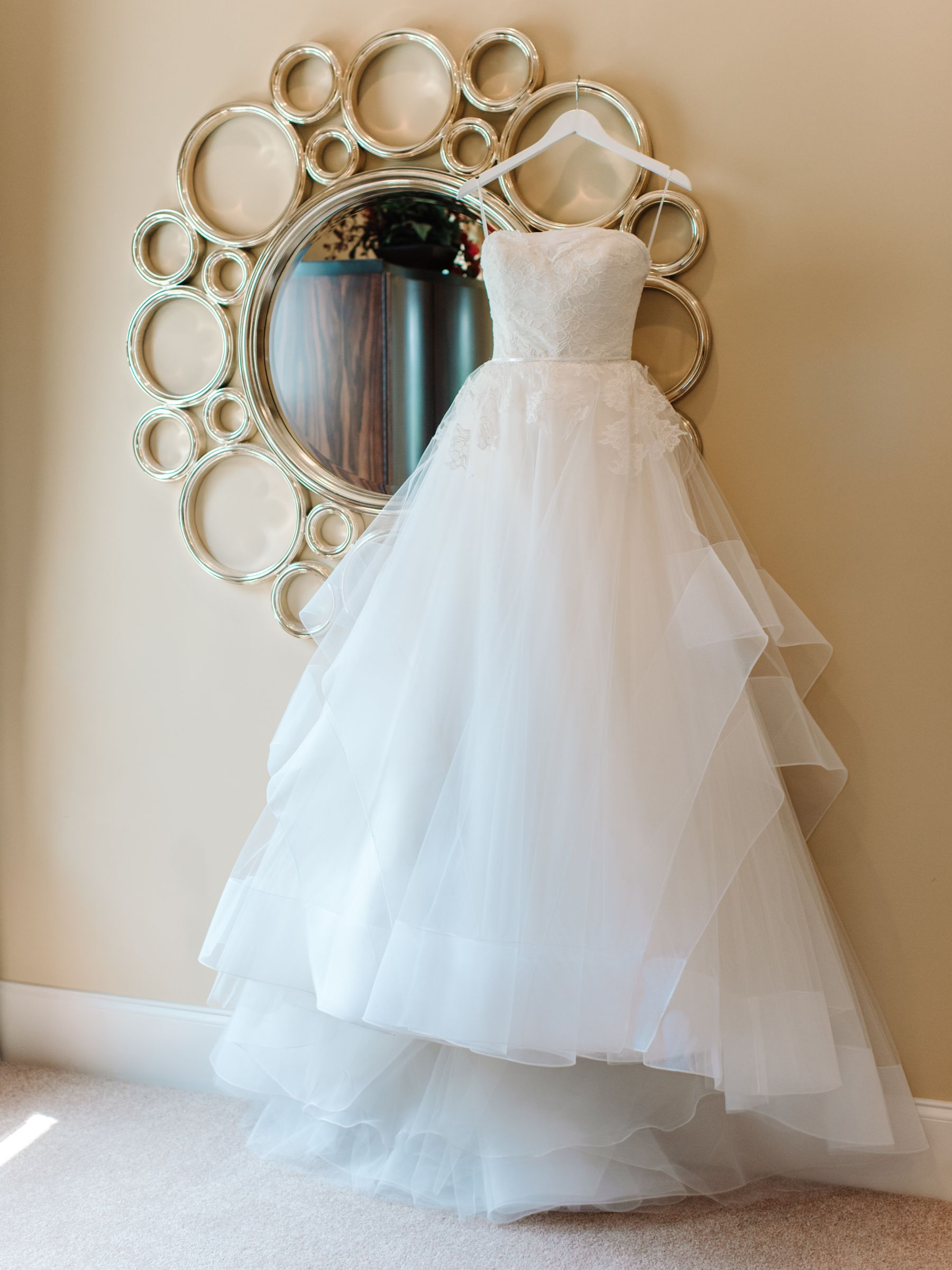 beautiful strapless wedding gown with tulle hanging by a mirror