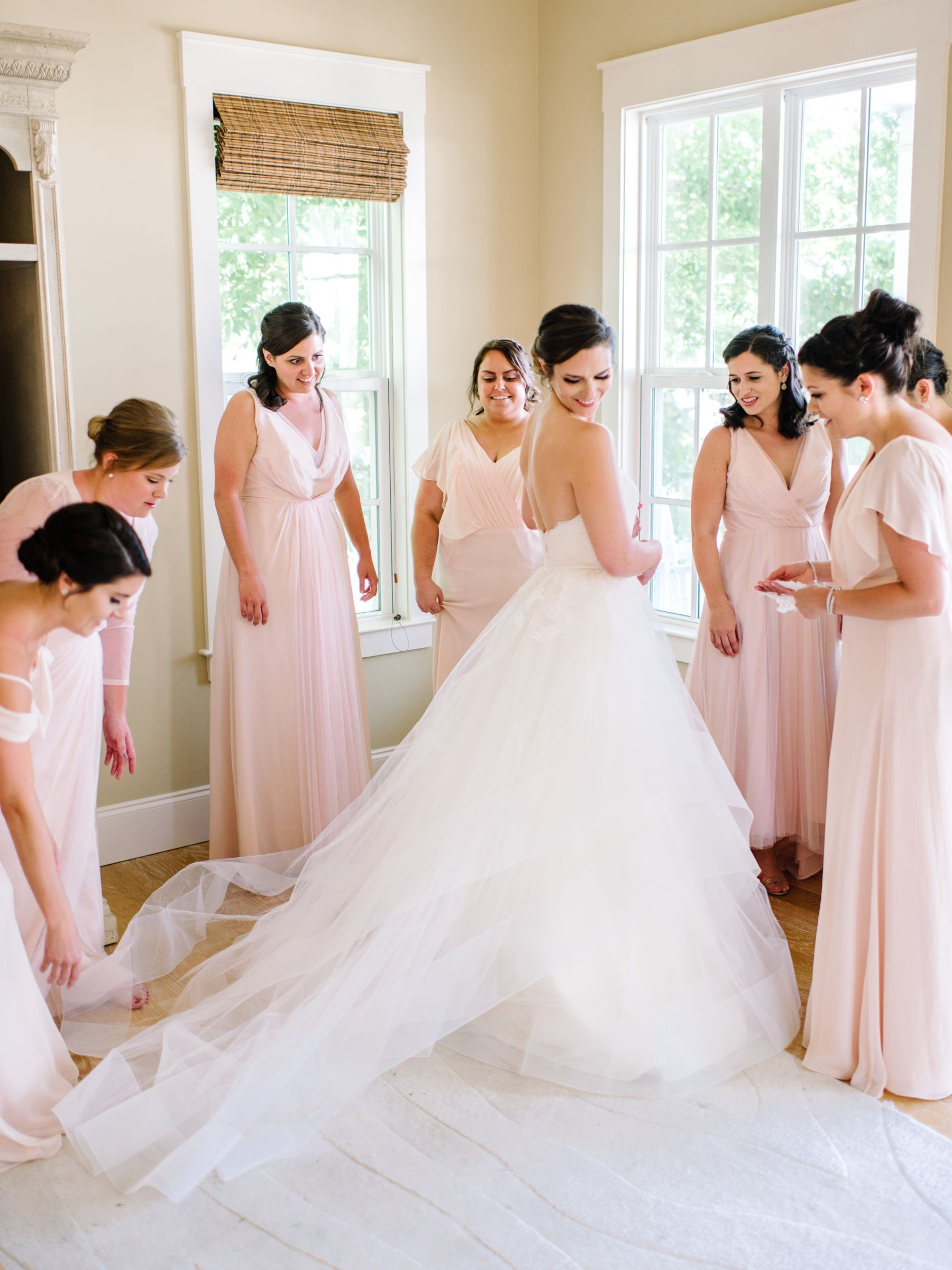 stunning bride surrounded by bridesmaids wearing blush gowns