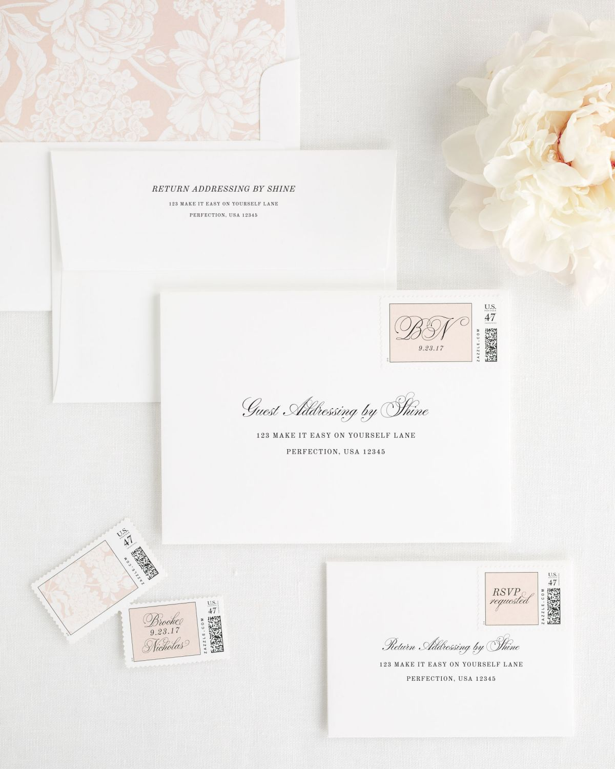 wedding envelopes with guest addressing and custom stamps in rose gold